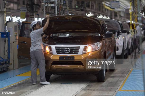 A worker inspects a Nissan Motor Co Navara pickup truck on an assembly line at the company's plant in Samut Prakan Thailand on Tuesday April 25 2017...