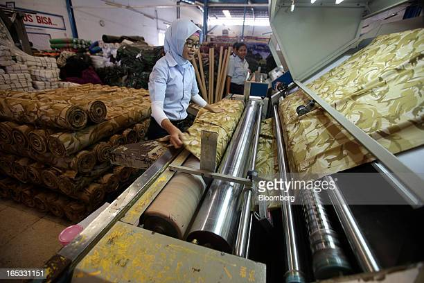 A worker inspects a roll of fabric in the printing area at a PT Sri Rejeki Isman factory in Sukoharjo Java Indonesia on Wednesday March 27 2013...