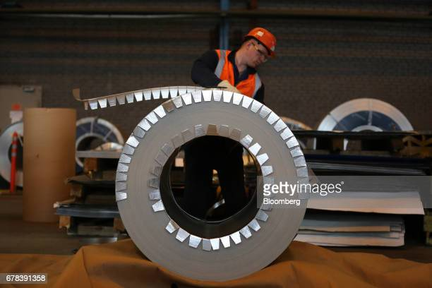A worker inspects a roll of steel sheet with a polymer coating in a storage area at the Cherepovets Steel Mill operated by Severstal PJSC in...