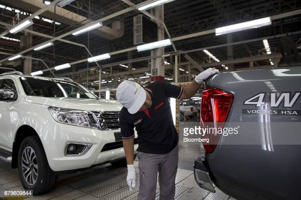 A worker inspects a tail light of a Nissan Motor Co Navara pickup truck on an assembly line at the company's plant in Samut Prakan Thailand on...
