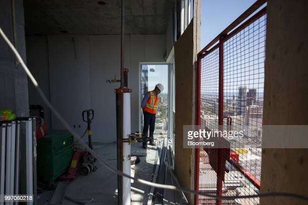 A worker inspects a unit during construction of the GWL Realty Advisors Livmore luxury apartment building in Toronto Ontario Canada on Tuesday July...