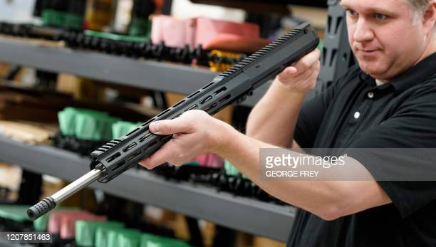 A worker inspects an finished AR15 rifle barrel at Delta Team Tactical in Orem Utah on March 20 2020 Gun stores in the US are reporting a surge in...