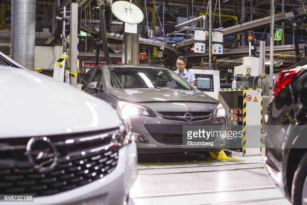 A worker inspects an Opel Astra automobile during quality control checks at the end of the production line at the Opel automobile plant in Gliwice...
