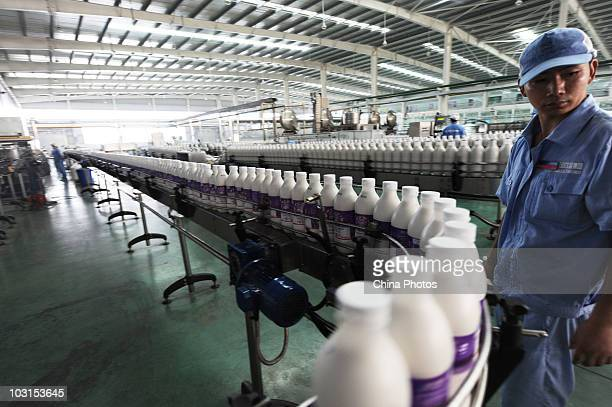 Worker inspects bottled beverages at a production line of the Bluesword Group's Drink And Food Industries on July 29, 2010 in Shifang of Sichuan...
