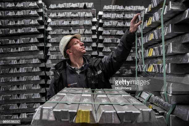 A worker inspects bound aluminum ingots stacked in a warehouse ahead of shipping at the Alumetal Group Hungary Kft aluminium processing plant in...
