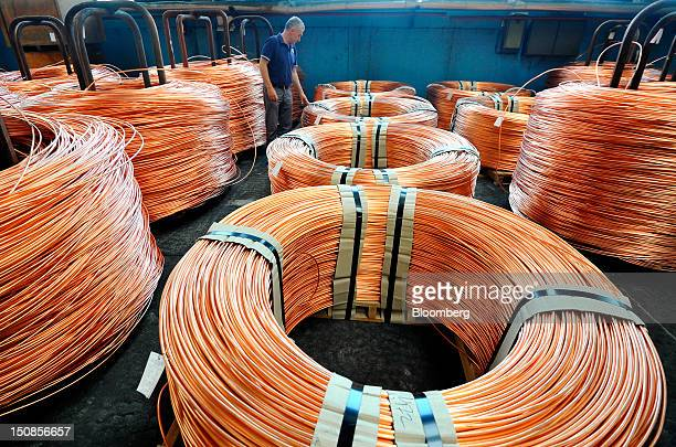 A worker inspects coiled bundles of 8mm copper wire before shipping in a warehouse at the copper mining and smelting complex operated by RTB Bor...