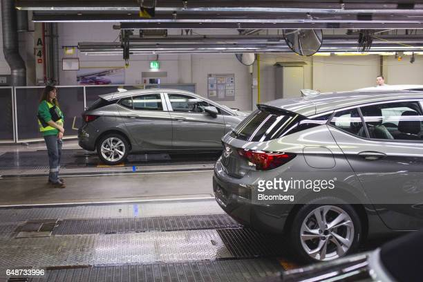 A worker inspects finished Opel Astra automobiles during quality control checks at the end of the production line at the Opel manufacturing plant in...