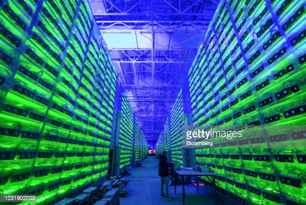 Worker inspects hardware devices as illuminated mining rigs operate inside racks at the CryptoUniverse cryptocurrency mining farm in Nadvoitsy,...