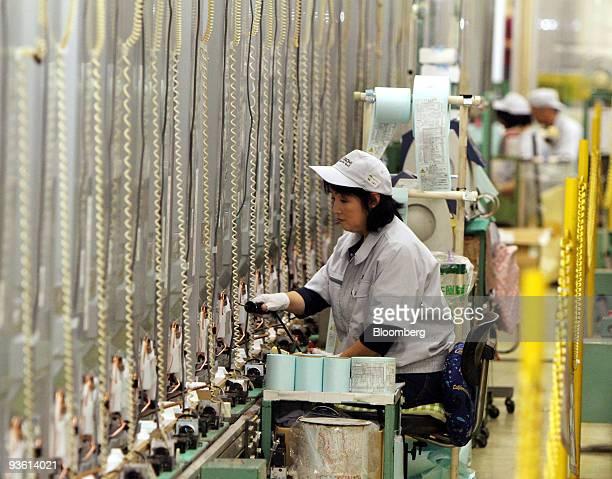 Worker inspects Hitachi Ltd. Refrigerators at Hitachi Appliances Inc.'s Tochigi plant in Tochigi prefecture, Japan, on Wednesday, Dec. 2, 2009....