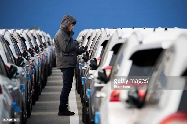 A worker inspects Kia Motors Corp vehicles bound for export at the port of Pyeongtaek in Pyeongtaek South Korea on Monday Jan 22 2018 Kia Motors is...