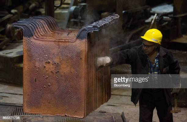 A worker inspects newly cast copper anode sheets at the MMC Norilsk Nickel PJSC copper refinery in Norilsk Russia on Thursday Oct 19 2017 Norilsk...