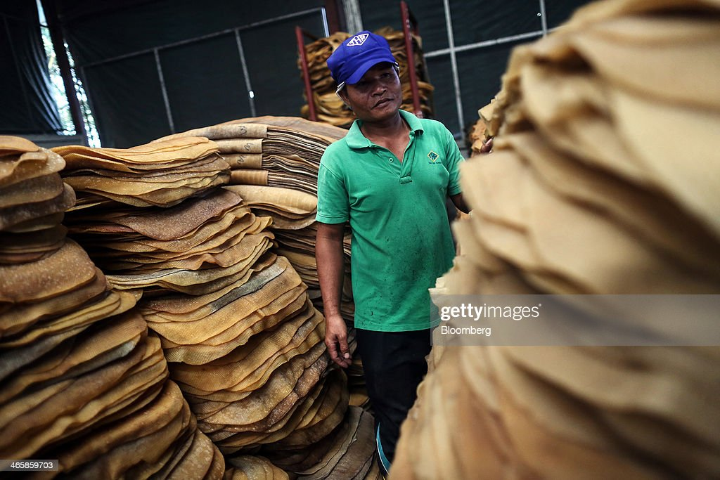 A worker inspects piles of smoked rubber sheets to be processed at the Thai Hua Rubber Pcl factory in Samnuktong, Rayong province, Thailand, on Wednesday, Jan. 29, 2014. Rubber production in Thailand, the world's largest exporter, may decline as growers from the main producing regions join protests seeking to overthrow the government, according to Von Bundit Co. Photographer: Dario Pignatelli/Bloomberg via Getty Images