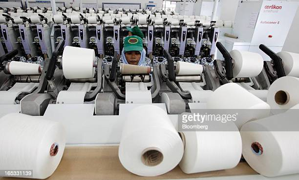 A worker inspects spools of yarn on a spinning machine in the spinning area at a PT Sri Rejeki Isman factory in Sukoharjo Java Indonesia on Wednesday...