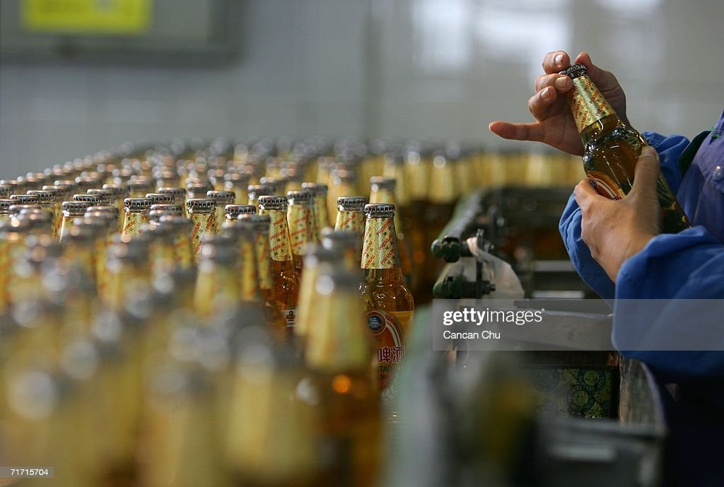 A worker inspects the bottles of Tsingtao beer before they are shipped out of the brewery at the Tsingtao beer factory on August 25, 2006 in Qingdao, Shandong Province of China. Tsingtao Beer Group, China's biggest beer brewery and the Official Domestic Beer Sponsor of the Beijing 2008 Olympic Games, hosts the 16th Qingdao International Beer Festival in Qingdao from August 12 to 26.