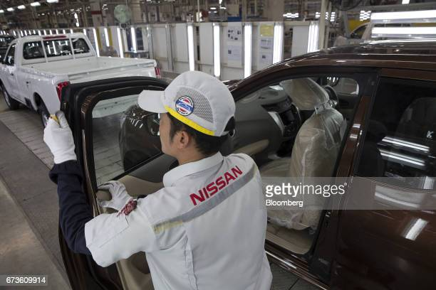 A worker inspects the door of a Nissan Motor Co Navara pickup truck on an assembly line at the company's plant in Samut Prakan Thailand on Tuesday...