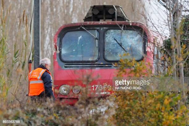 A SNCF worker inspects the front of a regional TER train that crashed into a school bus in Millas near Perpignan southern France on December 15 a day...