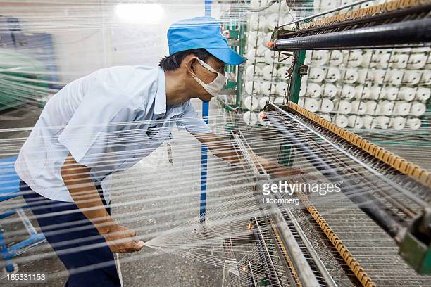 A worker inspects threads on a yarn machine in the spinning area at a PT Sri Rejeki Isman factory in Sukoharjo Java Indonesia on Wednesday March 27...