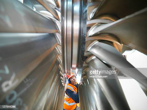 worker inspects turbine in power station - turbine stock photos and pictures