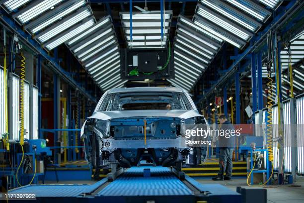 Worker inspects unpainted Ford Focus automobile bodies inside a light tunnel at the Ford Motor Co. Factory in Saarlouis, Germany, on Wednesday, Sept....