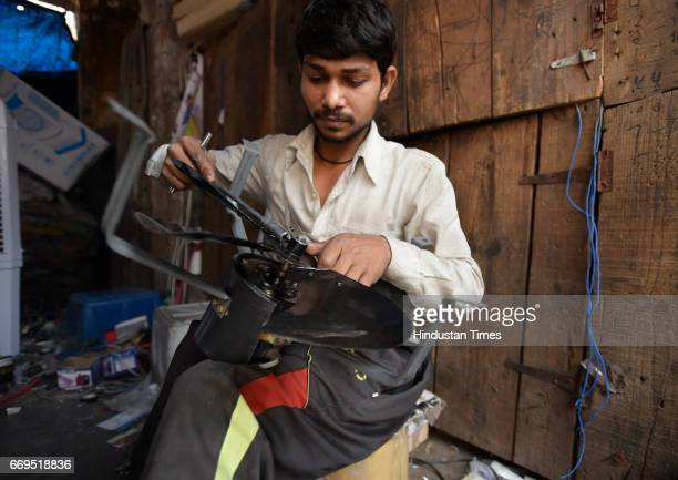 A worker installing air cooler in a shop at Kamla Market as temperature rises on April 17 2017 in New Delhi India Delhi residents continued to bear...