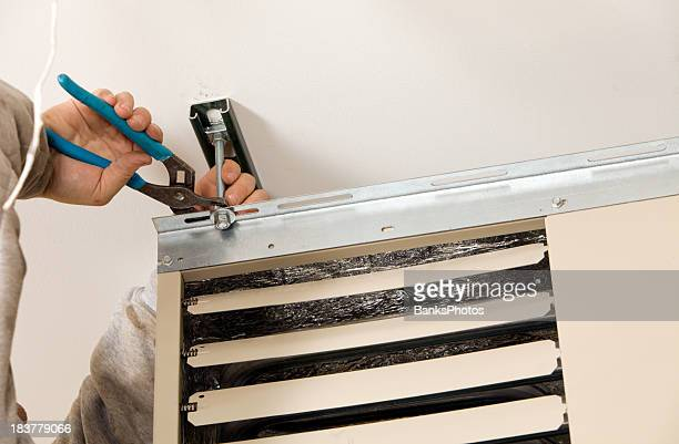 worker installing ceiling mounted gas heater - fastening stock pictures, royalty-free photos & images