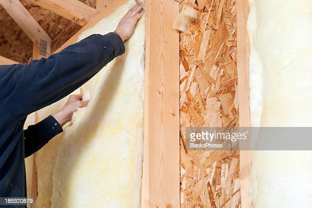 Worker Installing Fiberglass Batt Insulation between Wall Studs