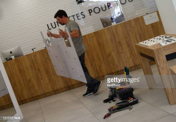 A worker installing Plexiglas screens on the counter of a shop intended to protect employees in Nantes France on May 7 2020 The shops and stores of...