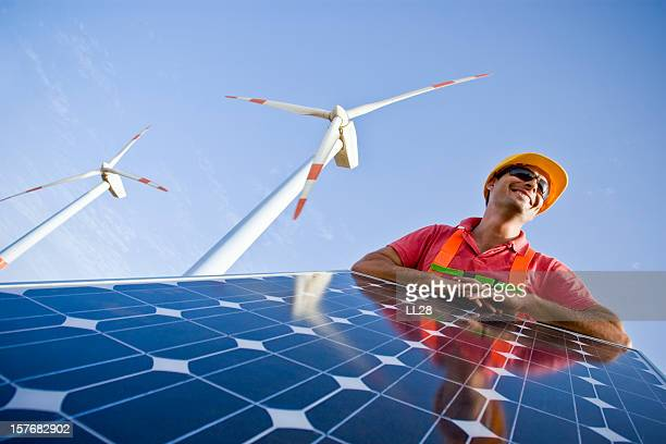 Worker installing solar panels and modern wind mills