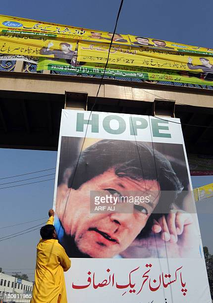 A worker installs a banner showing a portrait of Pakistani politician Imran Khan on a busy street in Lahore on October 27 2011 Tens of thousands of...
