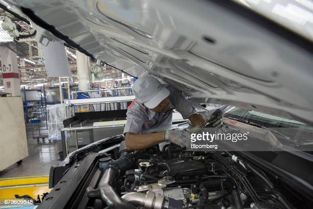 A worker installs a component into a Nissan Motor Co Navara pickup truck on an assembly line at the company's plant in Samut Prakan Thailand on...