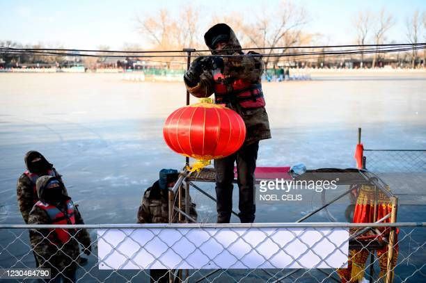 Worker installs a lantern by the icy Lake Houhai in Beijing on January 7 after China's meteorological authority recently issued a severe weather...