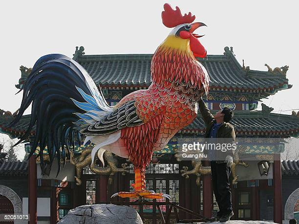 A worker installs a model of a rooster to mark the Chinese New Year on January 22 2005 in Beijing China China will usher in the lunar new year the...