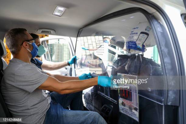 A worker installs a plexiglass barrier inside a taxi at Plexismart Srl in Guidonia close to Rome Italy on Wednesday May 20 2020 Floortoceiling...