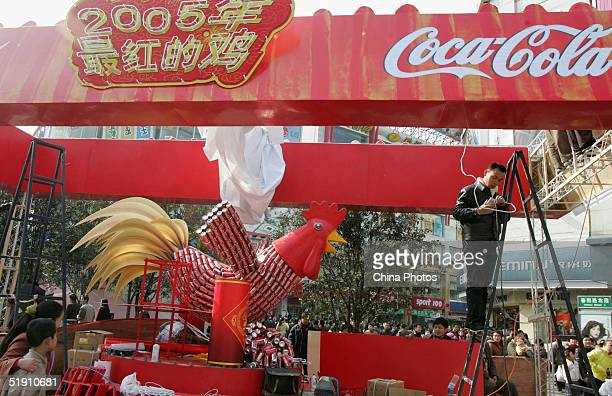 A worker installs a rooster with CocaCola cans on a street January 2 2005 in Chengdu China Festival promotions and marketing has started as the...
