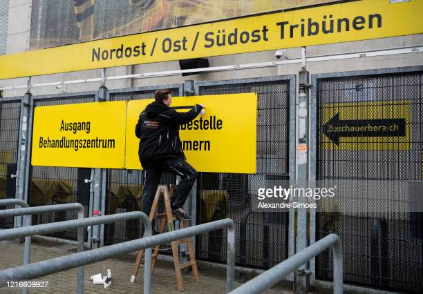 Worker installs a sign that marks the way to a coronavirus care facility at the north stand at Signal Iduna Park on April 3, 2020 in Dortmund,...