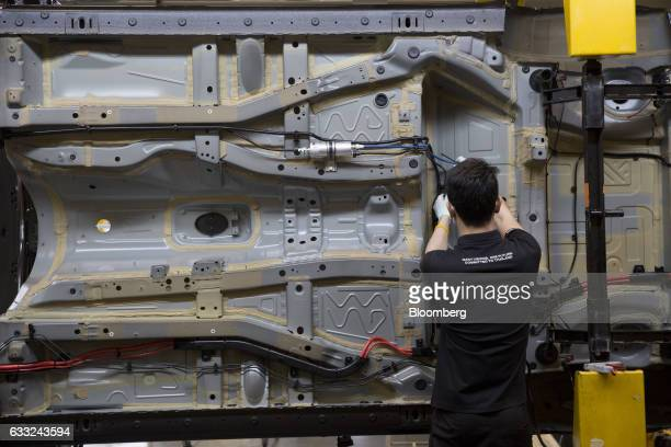 A worker installs a wire harness on a BMWX5 xDrive40e M Sport plugin hybrid vehicle at the BMW AG assembly plant in Amata Rayong province Thailand on...
