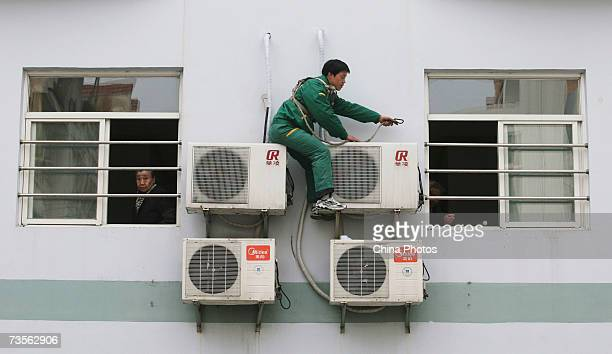 A worker installs air conditioners at a welfare center on March 13 2007 in Nanjing of Jiangsu Province China Qin Dahe head of the China...