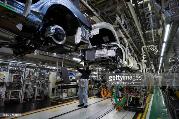 Worker installs an engine unit to a Toyota Motor Corp Crown vehicle on the production line of the company's Motomachi factory on July 30, 2018 in...