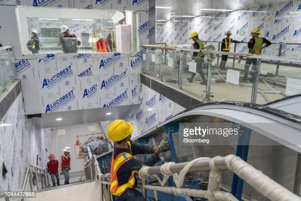 A worker installs an escalator at the under construction Jakarta Mass Rapid Transit Bundaran Hi station in the Thamrin area of Jakarta Indonesia on...