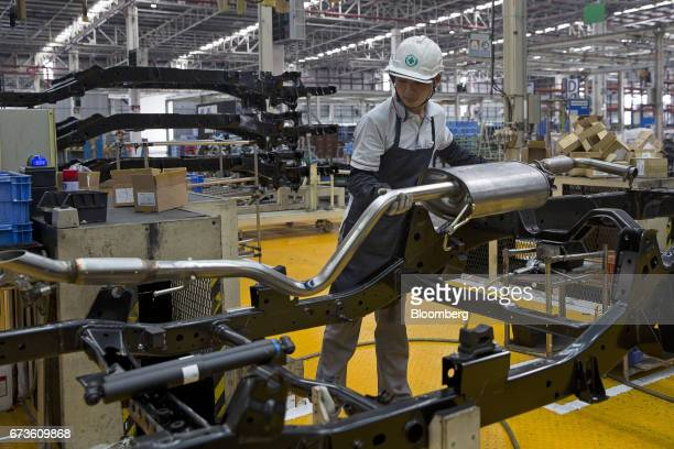A worker installs an exhaust pipe on the chassis of a Nissan Motor Co Navara pickup truck on an assembly line at the company's plant in Samut Prakan...