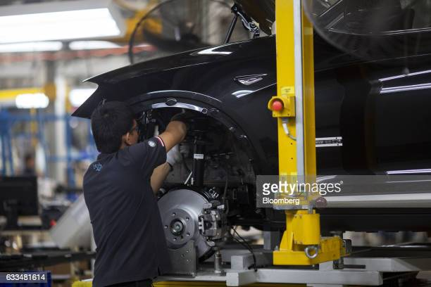 A worker installs cables on a BMWX5 xDrive40e M Sport plugin hybrid vehicle at the BMW AG assembly plant in Amata Rayong province Thailand on...
