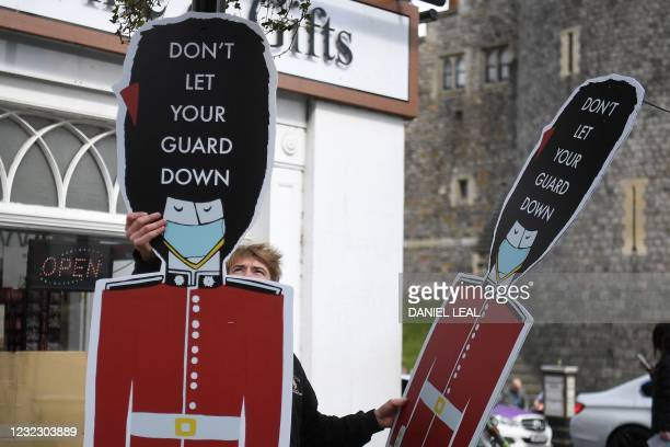 "Worker installs Covid-19 information signs depicting Coldstream Guards wearing face coverings, and the words ""Don't let your Guard down"", outside..."