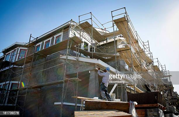 Worker installs exterior details on a house under construction at the KB Home's Whisler Ridge housing community in Lake Forest, California, U.S., on...