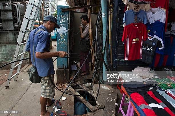A worker installs fiber optic cable underground in Yangon on September 14 2016 Rolling back US sanctions on Myanmar will top the agenda on September...