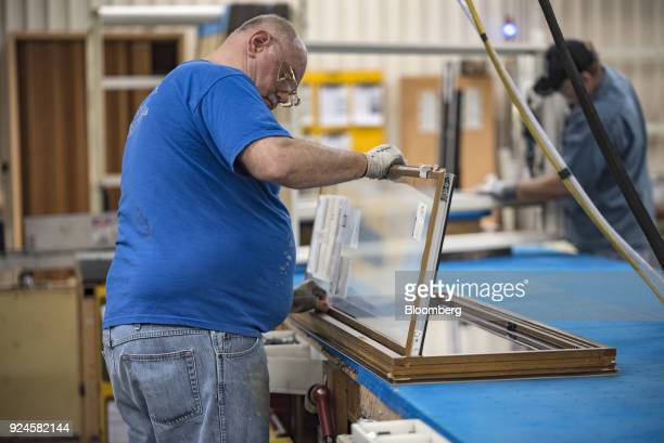 A worker installs glass to a window frame at the Pella Corp manufacturing facility in Pella Iowa US on Thursday Feb 22 2018 The US Census Bureau is...