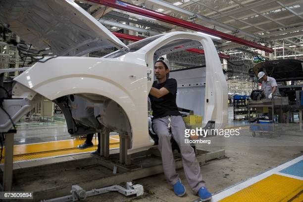 A worker installs interior components into the body of a Nissan Motor Co Navara pickup truck on an assembly line at the company's plant in Samut...