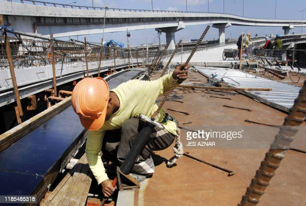 A worker installs iron supports while constructing a new section of the south Luzon expressway in Manila 31 January 2008 The Philippines economy grew...