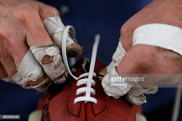 A worker installs laces on a football at the Wilson Sporting Goods Co factory in Ada Ohio US on Monday Jan 26 2015 Super Bowl XLIX features the...
