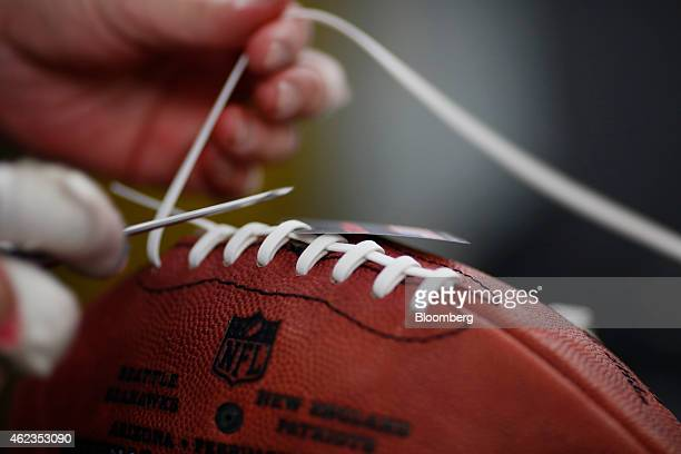 A worker installs laces on a Super Bowl XLIX branded football at the Wilson Sporting Goods Co factory in Ada Ohio US on Monday Jan 26 2015 Super Bowl...