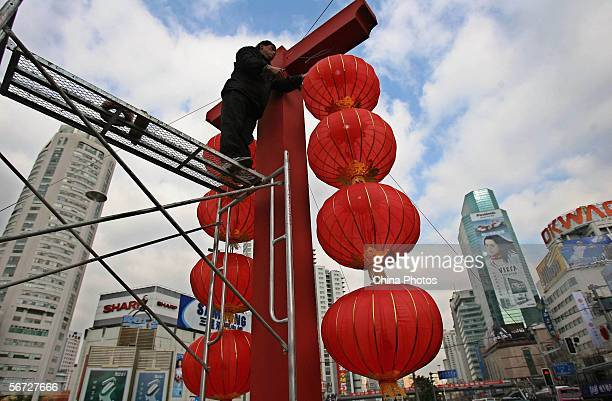 A worker installs lanterns for New Year's celebration on a street in the business district February 1 2006 in Shanghai China China is celebrating the...